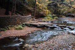 优美的瀑布在一座石走道和桥梁附近流动 免版税库存照片