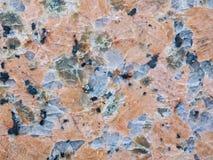 优美的红色花岗岩石头表面纹理的特写镜头  免版税库存照片