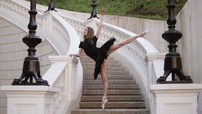 优美的芭蕾运动的正面图 年轻人,做垂直的麻线和摆在站立在a的白肤金发的头发的芭蕾舞女演员 股票视频