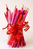 优美的铅笔、红色和粉色标志和笔花束,栓与猩红色丝带 免版税库存照片