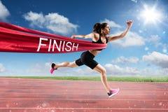 优胜者在终点线的妇女赛跑者 免版税库存照片