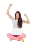 优胜者女孩坐与膝上型计算机的地板 免版税图库摄影