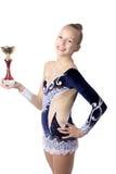 优胜者拿着第一个地方杯子的体操运动员女孩 库存图片