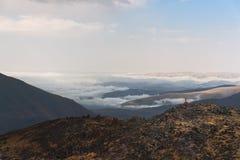 优胜者站立在一个岩石边缘用在谷前面被上升的棍子盖由在的云彩的远足者 库存照片