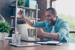 优胜者!年轻美国黑人的企业家的梦想实现 他是非常激动,佩带的聪明偶然的,庆祝在  免版税图库摄影