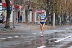 优胜者Oleksandra跑在城市街道上的Shafar在马拉松的乌克兰冠军期间在成人中 免版税库存照片