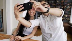 伙伴在手机的作为selfies在工作区 股票录像
