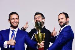 伙伴庆祝赢取的竞争 公司领导拿着金黄奖 免版税图库摄影