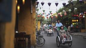 会安市,越南- 2018年5月10日:人力车驱动沿古老街道的中国游人在老镇在Hoian 影视素材