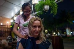会安市,越南- 2018年4月19日:白种人女孩在会安市享受脖子按摩 图库摄影