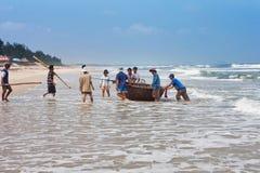 会安市,越南- 2011年11月03日:越南人从从海洋的渔回来并且运载一条地道圆的越南蟒蛇 免版税库存照片