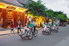 会安市,越南- 2017年3月15日:乘坐一个传统周期的地方越南人在会安市 会安市,联合国科教文组织世界遗产名录站点 库存图片