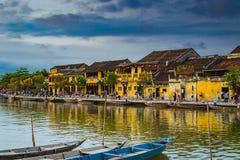 会安市,越南- 2017年3月17日:在古老建筑学前面的传统小船在会安市,越南 免版税库存图片