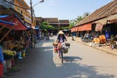 会安市,越南- 2013年4月13日:地方老妇人是在自行车在会安市市场上 免版税库存照片