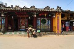 会安市,越南- 2013年4月13日:垃圾收集工和她的自行车,会安市古镇 库存照片