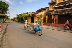 会安市,越南- 2014年5月12日:垃圾收集工和她的自行车,会安市古镇 库存图片