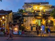 会安市,越南- 2015年11月8日:街道场面,在餐馆前面的游人,平衡光 图库摄影