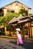 会安市, QUANG NAM,越南, 2018年4月26日, :佩带ao戴的越南妇女 与老房子的街道视图在会安市古镇 免版税库存图片