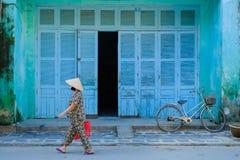 会安市/越南,12/11/2017:有通过在传统房子蓝色前面的一辆自行车旁边的米帽子的地方越南妇女 库存图片