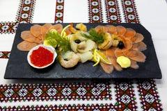 宴会菜单 钓鱼在一个美丽的黑盛肉盘的分类有红色鱼的,虾,鱼子酱,熏制鲑鱼,比目鱼 一道伟大的开胃菜 库存照片