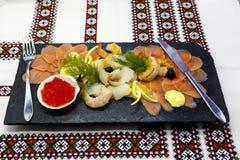 宴会菜单 钓鱼在一个美丽的黑盛肉盘的分类有红色鱼的,虾,鱼子酱,熏制鲑鱼,比目鱼 一道伟大的开胃菜 库存图片