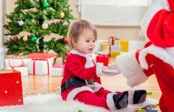 会见圣诞老人的小女孩由圣诞树 库存照片