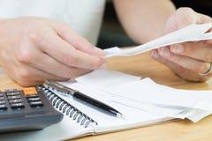 会计、费用或者企业经营情况的演算概念,拿着财政费用票据或收据与计算器和笔的手 库存图片