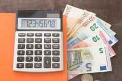 会计和业务管理钞票,计算器在木背景的andEuro钞票 税、借方和费用的照片 免版税库存图片