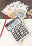 会计和业务管理钞票,计算器在木背景的andEuro钞票 税、借方和费用的照片 图库摄影