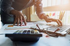 会计工作分析关于膝上型计算机的财政报告在他的 免版税库存图片