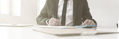 会计文字笔记和工作与一个手工计算器 免版税库存图片