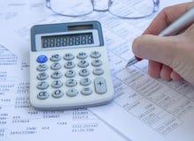 会计科目背景计算器概念现有量查出在白色 有财务纸和人手的w计算器 免版税库存图片
