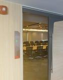 会议室前面以空置标记的状态和从窗口的火警通知木桌阳光 免版税图库摄影