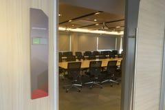 会议室前面以空置标记的状态和从窗口的火警通知木桌阳光 库存图片