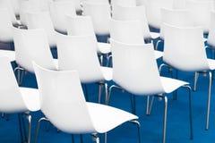 会议椅子在企业屋子里,白色塑料舒适的位子行在空的公司颁奖大会办公室,细节 免版税库存图片