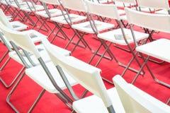 会议椅子在企业屋子里,白色塑料舒适的位子行在空的公司颁奖大会办公室,细节 免版税图库摄影