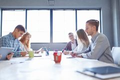 会议的企业职员 编组关于轻的室背景的办公室讨论 配合概念 免版税库存图片