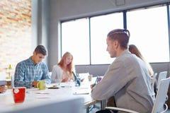 会议的企业职员 编组关于轻的室背景的办公室讨论 配合概念 免版税图库摄影