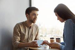 会议饮用的咖啡的两位年轻pesrpective企业家,谈论未来起始的项目和看throug 库存照片