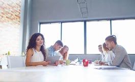 会谈的可爱的女商人与办公室背景的同事 办公室会议概念 免版税库存照片