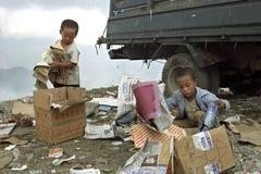 会集在垃圾填埋的可怜的菲律宾男孩老纸 库存照片