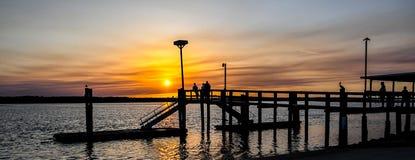 会集在日落壮观的渔码头 库存照片