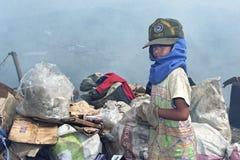 会集塑料,在垃圾填埋的纸的可怜的菲律宾男孩 免版税库存图片