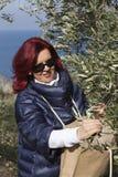 会集橄榄叶子的俏丽的妇女 库存照片