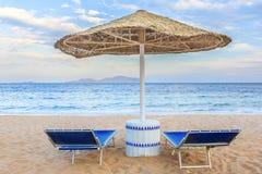 伞和两空的deckchairs在岸沙子靠岸 免版税库存图片