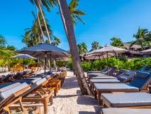 伞和椅子在海滩和海海洋有蓝天的 库存图片