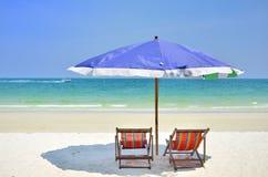 伞和椅子在海滩在蓝天 免版税库存照片