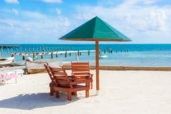 伞和椅子在海滩在Caye填缝隙工,伯利兹 库存图片