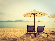 伞和椅子在热带海滩海和海洋日出时间的 免版税库存照片