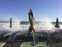 伞和海滩睡椅在风大浪急的海面期间 库存照片